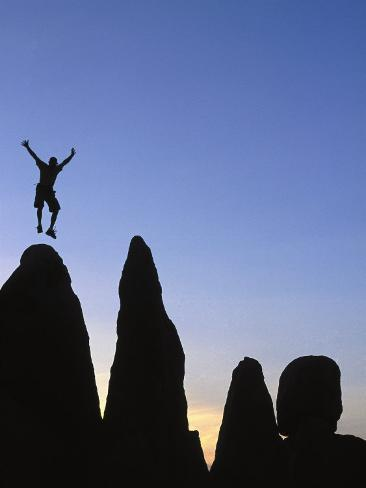 Silhouette of Man Jumping on Top of Rock Photographic Print