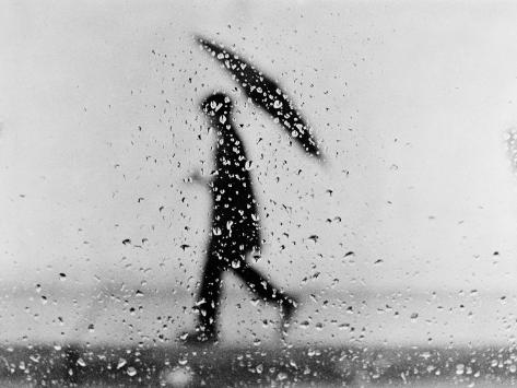 Silhouette of Man Carrying an Umbrella, Walking in the Rain Photographic Print