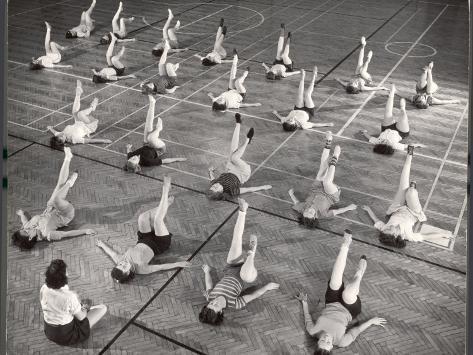 Girls and Women Doing Leg Exercise on Floor of Metropolitan Life Insurance Company's Gym Photographic Print