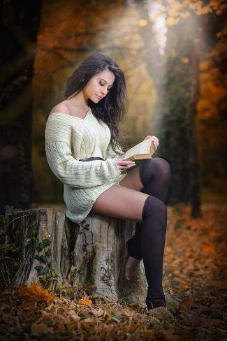 young caucasian sensual woman reading a book in a romantic autumn