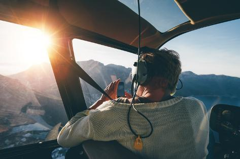 Rear View of Female Tourist on Helicopter Tour Taking Pictures While Flying over Mountains on a Sun Photographic Print