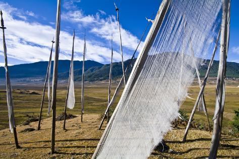 The Translucent Cloth of a Prayer Flag Fluttering in the Wind Above a Himalaya Wetland Photographic Print