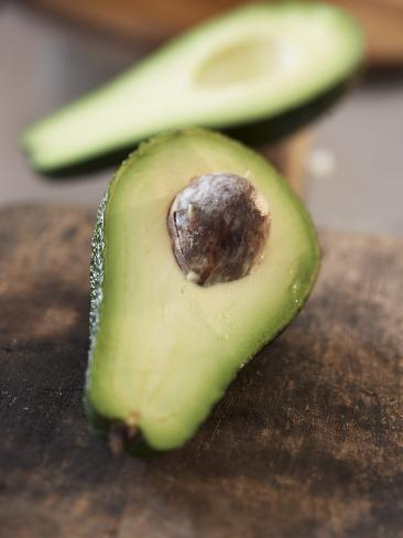 Avocado, Halved, on Old Chopping Board Photographic Print