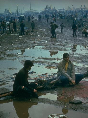 Chuck Morgan Sitting in the Mud and Water with a Friend, During Woodstock Music and Art Fair Photographic Print