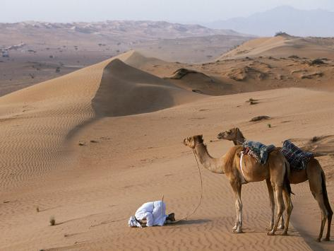 Kneeling to Pray in Desert, Holding Camels by Halters to Prevent Them Wandering Off Amongst Dunes Photographic Print