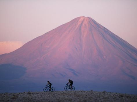 Mountain Biking in Atacama Desert Against a Backdrop of Perfect Cone of Volcan Licancabur 5916 M Photographic Print