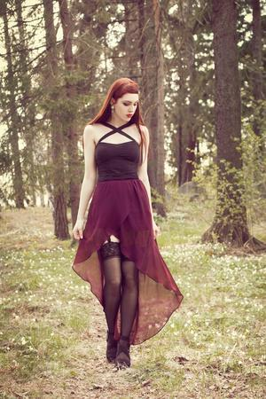 Young Redhead Woman In A Dress And Stockings Looking Down