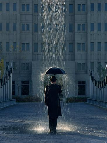 man with umbrella under a regional rain photographic print by joseph