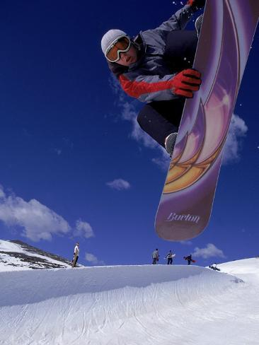 Snowboarder with Colorful Board Doing a Trick Photographic Print
