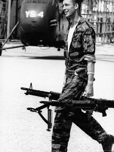 Yankee Papa 13 Helicopter Crew Chief James Farley Carrying a Pair of M-60 Machine Guns Photographic Print