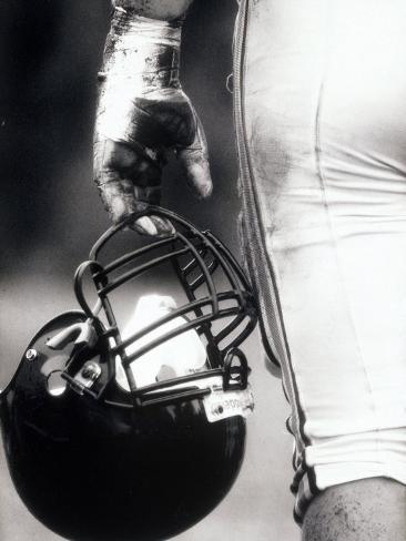 Low Angle View of An American Football Player Holding a Helmet Lámina fotográfica