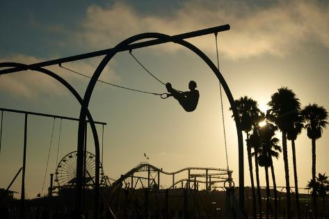 As the Sun Sets a Silhouetted Man Works out on Gymnast Rings Photographic Print