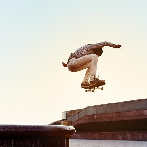Skateboarder Performs a Trick in the City on a Sunny Day Photographic Print