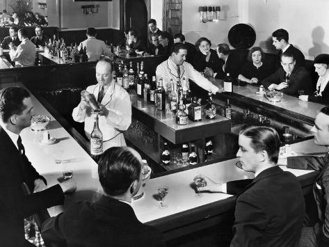 Bartender Prepares a Drink as Patrons Enjoy Themselves at Popular Speakeasy during Prohibition Photographic Print