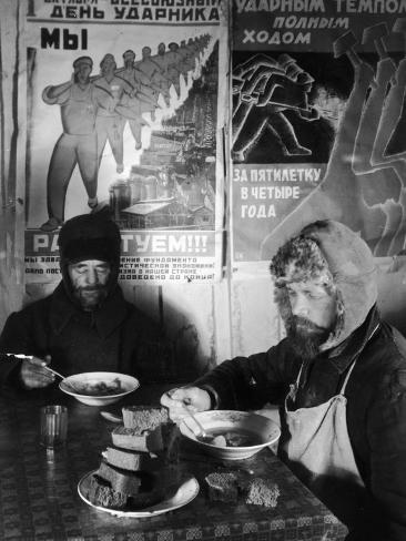 Russian workers eating black bread and soup at table with soviet communist workers posters siberia