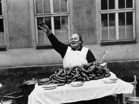 Vendor Trying to Sell Bundles of Sausage Valokuvavedos