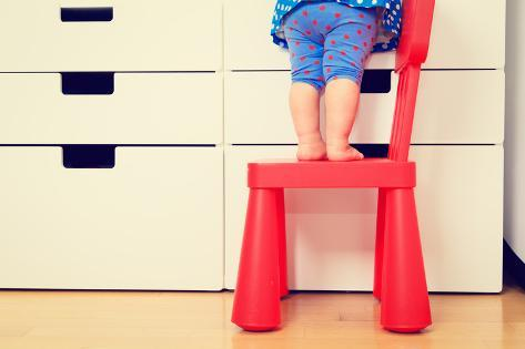 Kids Safety Concept- Little Girl Climbing on Baby Chair Photographic Print