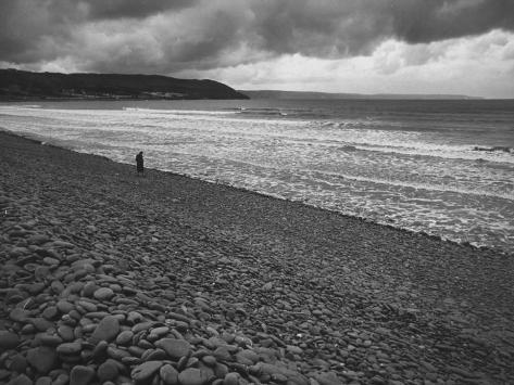 Along British Coastline, Woman Walking on Pebbled Shore Photographic Print