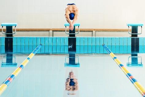 Young Muscular Swimmer Jumping from Starting Block in a Swimming Pool Photographic Print