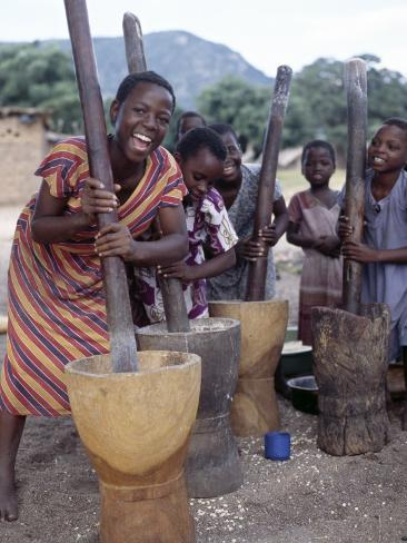 Cheerful Young Girls Pound Corn Outside Families' Homes Near Monkey Bay, South End of Lake Malawi Photographic Print