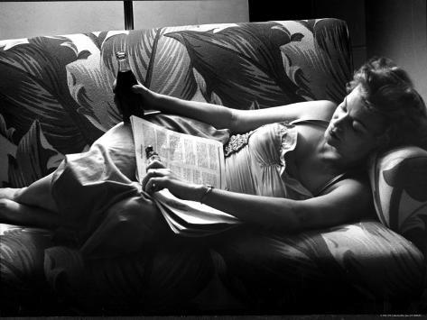 Woman Relaxing on Sofa, Reading and Drinking a Coke Photographic Print
