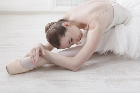 Beautiful Graceful Young Ballerina in Pointe Shoes at White Wooden Floor Makes Ballet Leg Stretchin Photographic Print