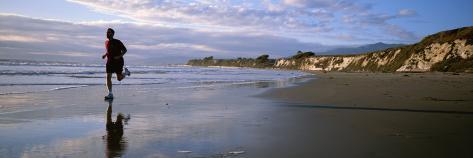 A Man Jogs Along Sands Beach Below Ellwood Bluffs, at Sunset Photographic Print