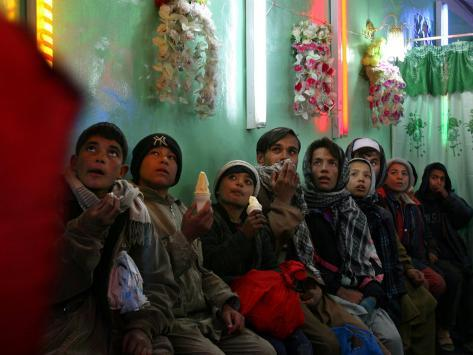 Afghan Boys Watch a Movie on a Television, Unseen, as They Eat Ice Cream at an Ice Cream Shop Fotoprint