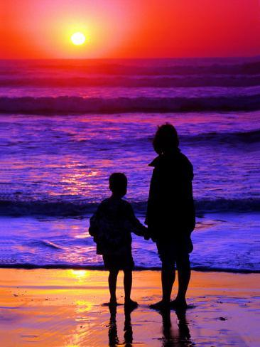 Sunset Silhouette of Mom and Boy Along Coast Photographic Print
