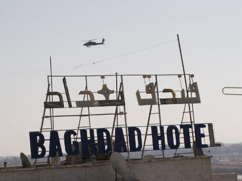AH-64 Apache in Flight over the Baghdad Hotel in Central Baghdad, Iraq Photographic Print