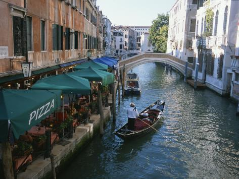 A Gondolier Passes a Restaurant on a Canal in Venice, Italy Photographic Print
