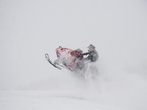 A Snowmobiler Jumps from a Hill on a Snowy Day Photographic Print