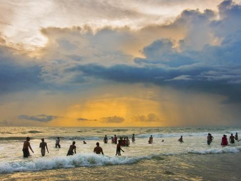 Indian Bathers Playing in Surf During Cloudy Sunset Photographic Print