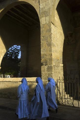 Three Nuns Walking Outside the Santa Maria Del Camino Church Photographic Print