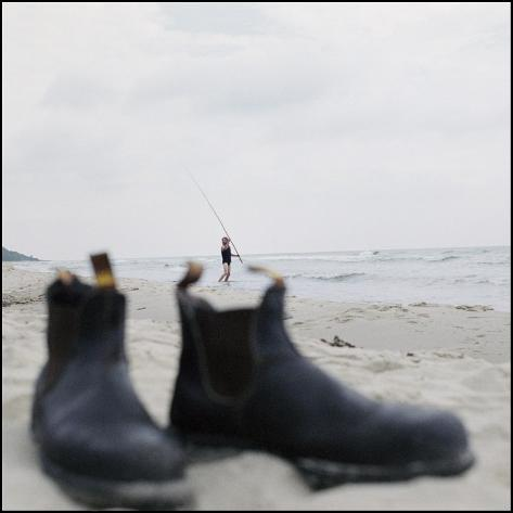 Close-Up of a Pair of Boots with a Man Fishing on the Beach in the Background, Sweden Stretched Canvas Print