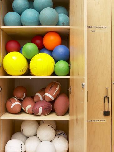 Various Sports Balls Arranged On Shelves Of Wooden Storage Closet  Photographic Print