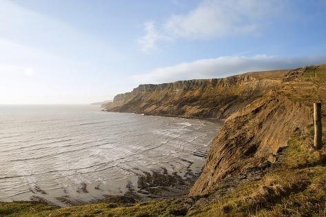 Beautiful Coastal Landscape at Sunrise with Cliffs and Misty Glow Photographic Print