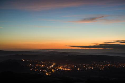 Pre-Sunrise Landscape Overlooking Brightly Lit Town in Valley in Winter Photographic Print