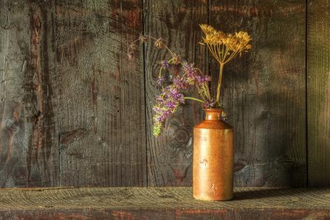 Retro Style Still Life of Dried Flowers in Vase against Worn Wooden Background Photographic Print