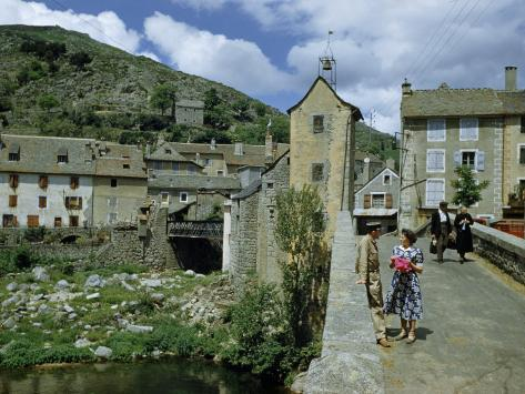 People in Riverside Village Walk across an Old Bridge Photographic Print
