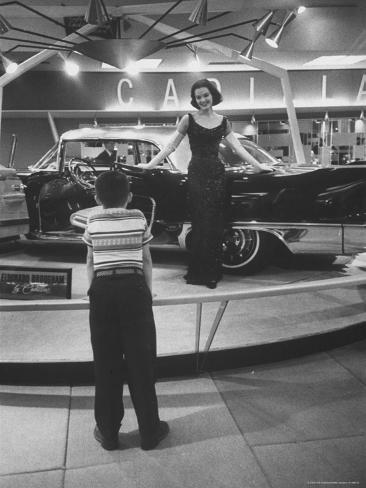 Model Posing Beside Cadillac Eldorado Captures Attention of Young Boy at National Automobile Show Photographic Print