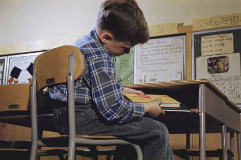 Schoolchild Placing Books in Desk Valokuvavedos
