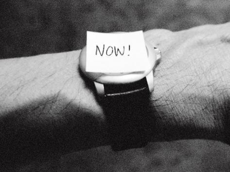 The Word Now as a Reminder Attached to a Watch on a Male Arm Photographic Print