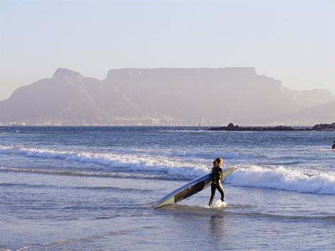 Young Woman Surfer Enters the Water of the Atlantic Ocean with Table Mountain in the Background Photographic Print