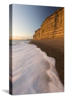 Foam on beach below cliffs at Burton Bradstock, Dorset, UK by Ross Hoddinott