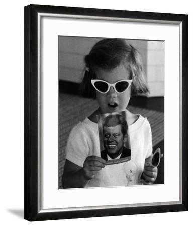 Caroline Kennedy holds a Postcard of her Father, 1961