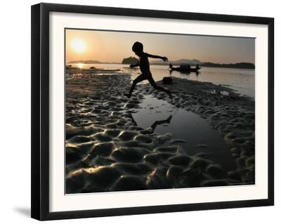 A Boy Plays on the Banks of the River Brahmaputra in Gauhati, India, Friday, October 27, 2006