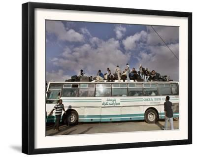 Palestinians Sit on Top of a Bus