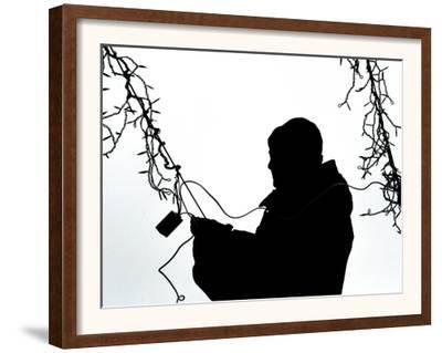 An Man Wires Christmas Lights