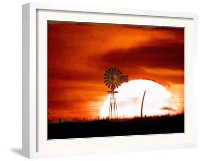 A Blazing Sun Drops Behind a Windmill